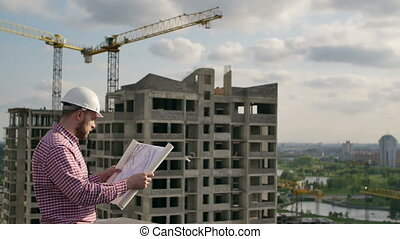 Man architect inspects the construction site