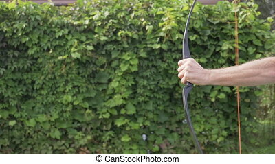 Man arm is shooting with a bow. Close-up view. Slow motion.