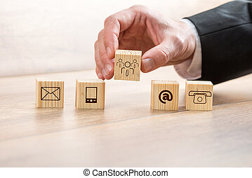 Man Arranging Wooden Cubes with Contact Symbols