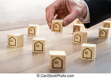 Man Arranging Wooden Cubes with House Drawings