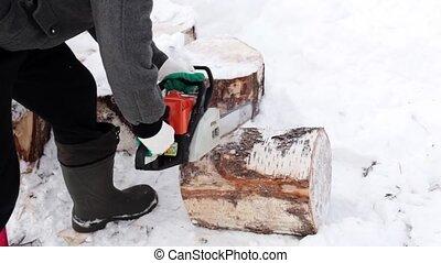 man as a saw cuts wood