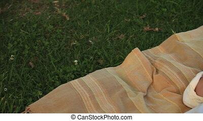 Man asleep on a rug outdoors