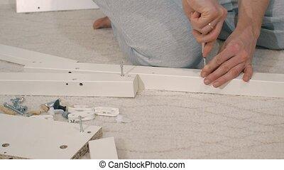 Man assambling wooden furniture - Man's hands assambling...