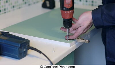 man assembles furniture using a power screwdriver