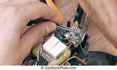 Man assembling FPV drone using tools, preparing quadcopter...
