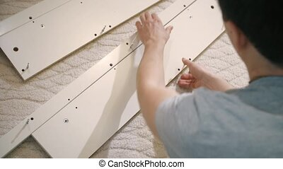 Young man assembling a piece of furniture