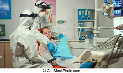 Man assistant in protective suit putting dental bib to kid before stomatological examination during covid-19 pandemic. Concept of new normal dentist visit in coronavirus outbreak wearing coverall