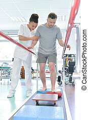 man assisted by nurse in rehab clinic