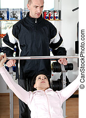 man assisting woman weitght lifting at a gym