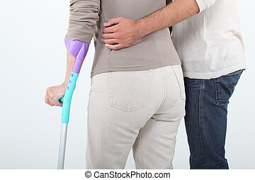 Man  assisting woman with crutches
