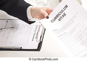 man at a a job interview with  interviewer, giving her his resume