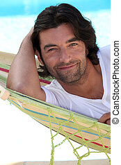 Man at beach laid in hammock