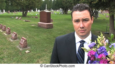 Man at Cemetery - Sad man stares into camera with flower...