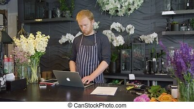 Man at counter in shop - Young redhead man in striped apron...