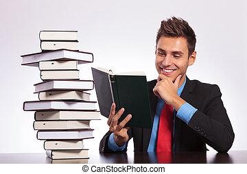 man at desk reading book