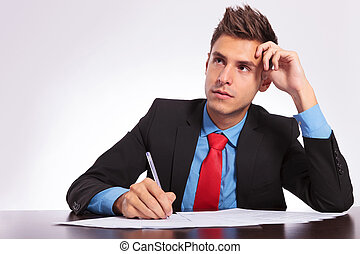 man at desk thinking what to write - young business man...