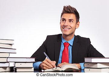man at desk thinking & writing