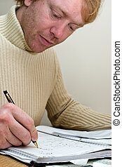 Man at desk working with a pen and paper