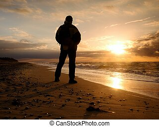 Man at evening sea. Hiker with backpack with hands in pocket along beach.