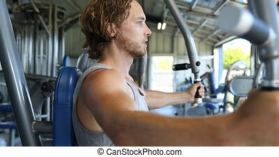 Man at fitness gym doing butterfly chest workout on fitness fly machine