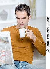 man at home reading newspaper drinking beverage