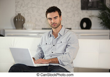 Man at home typing on computer