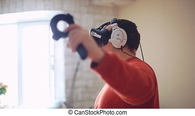 Man at home wearing Virtual Reality Headset and headphones Playing Game. 1920x1080