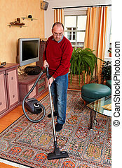 Man at home with a vacuum cleaner - Man cleans the apartment...