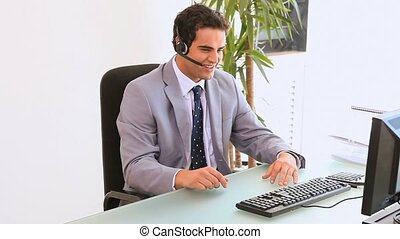 Man at is desk talking on his headset