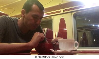 man at night eating soup in the train restaurant lifestyle...