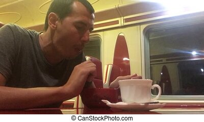 man at night eating soup in the train restaurant railway cat...