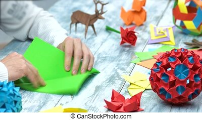 Man at origami folding lesson. Collection of beautiful...
