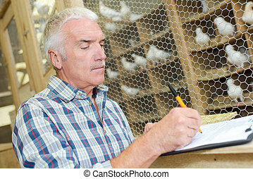 Man at pigeon coop writing on clipbaord