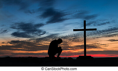 Man At Prayer Cross - Sunset behind a man praying next to a...