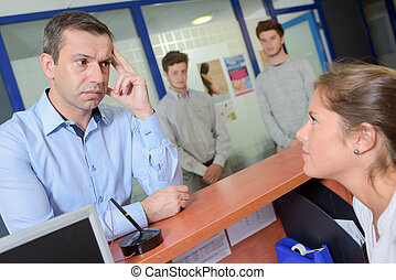 Man at reception desk, looking worried