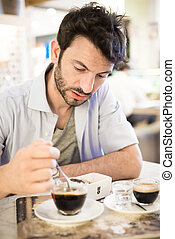 man at the bar drinking coffee
