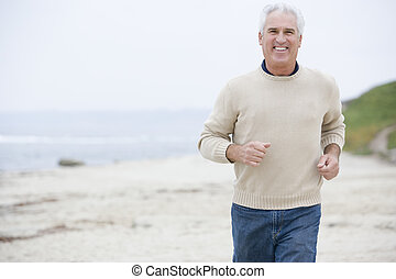 Man at the beach running and smiling