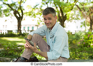 Man at the park using a tablet