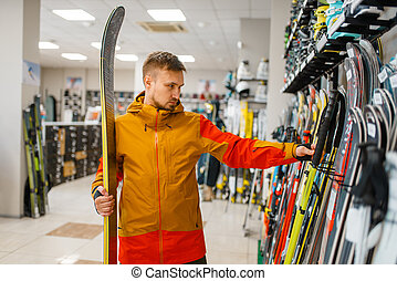 Man at the showcase choosing downhill ski, shopping in sports shop. Winter season extreme lifestyle, active leisure store, customer buying skiing equipment