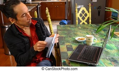 Man at the table is working with laptop