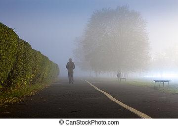 Man at urbanized path during misty weather - Walking man on...