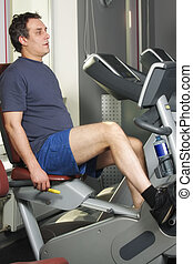 Man at workout on bicycle machine