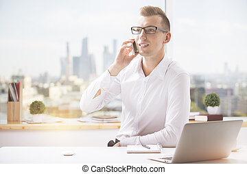 Man at workplace talking on phone