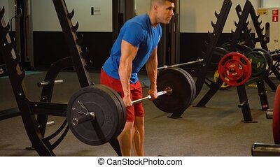 Man athlete doing exercises on back with barbell in the gym