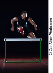 athlete jumping over a hurdles - man athlete jumping over a...