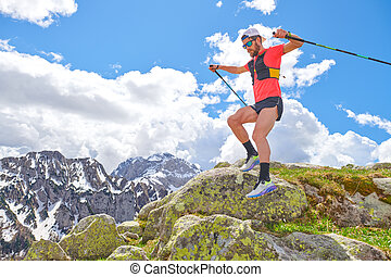 Man athlete jumps between the stones during a trail workout in the mountains