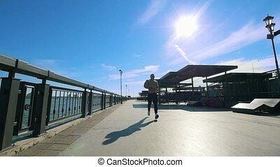 Man athlete - muscular male is jogging on the promenade at sunny day, slow-motion