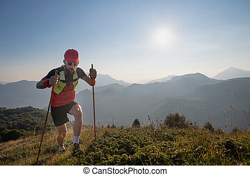 Man athlete of sky-raid in the mountains with poles sticks uphill