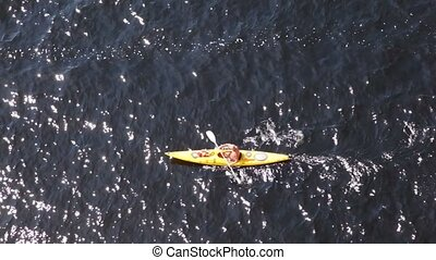 Man athlete quietly floats in yellow canoe in sunny day