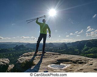 Man athlete runner with trekking poles running rocky trail